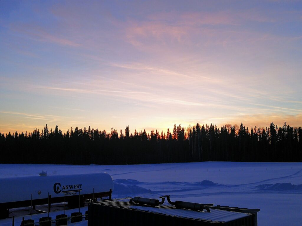 Sunset outside of Fort Nelson with beautiful pink glow on the sky and purple hue on the snow