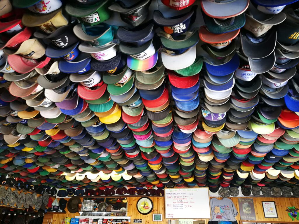 Numerous baseball caps covered the ceiling of Toad River Lodge