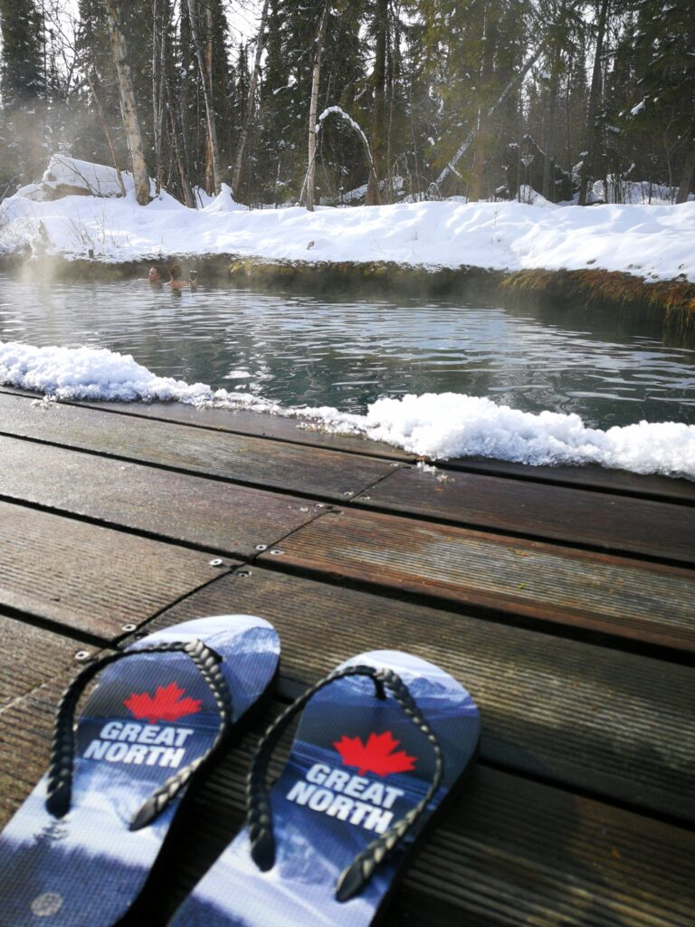 Slippers with The Great North and Canadian flag by the Liard Hot Springs pool