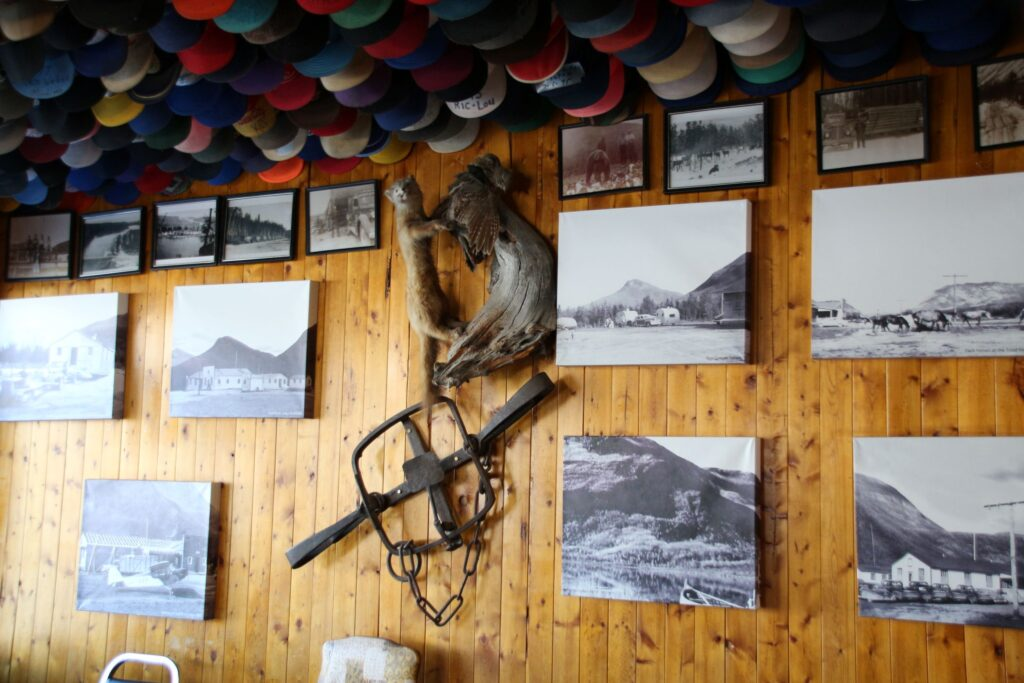 Historic photos, old horse harness decorating the wall of Toad River Lodge