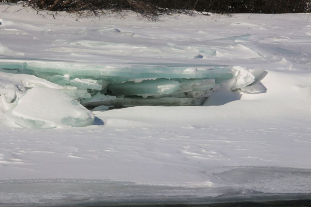 Ice started to melt on Toad River, creating layers of blue and green ice sheet