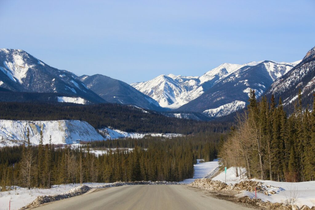 Winding scenic road through the forest with snow peaks in the distance
