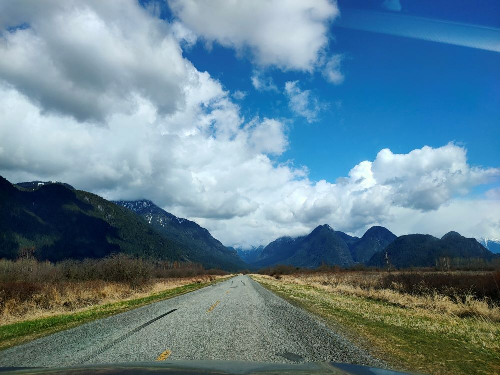The view of Rannie Road leading to Pitt Lake with clouds and mountains