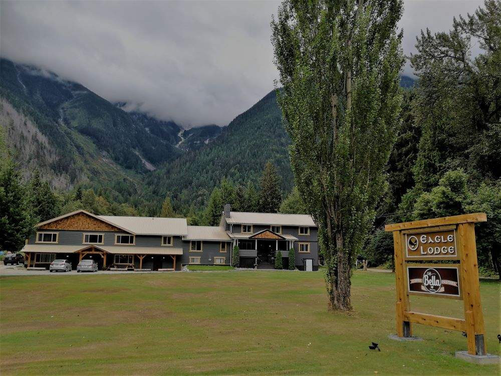 The front view of Bella Coola Eagle Lodge with signage and clouds covered mountains at the back