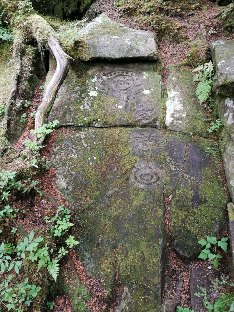 Petroglyphs of a man's face, ravens and the sun