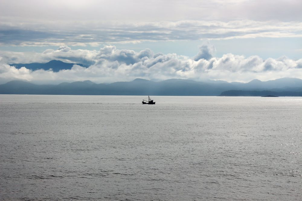 The view of Namu with dramatic clouds and a fishing boat in front the coast line