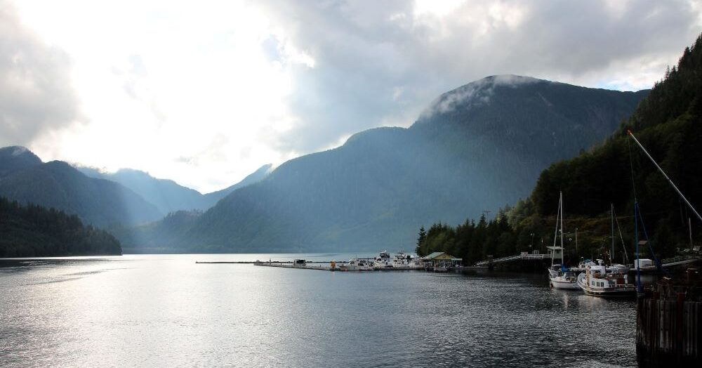 Ocean Falls Harbour with leisure boats moorage, beautiful sunlight pierced through the clouds